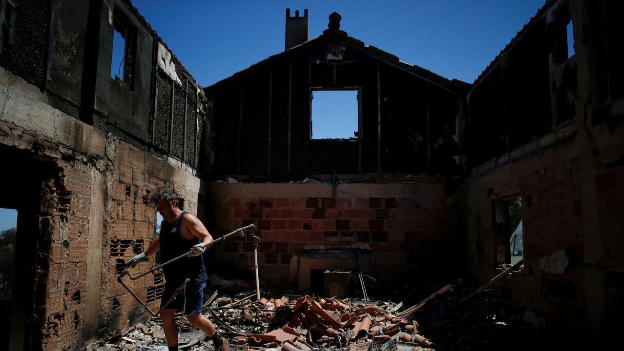 Anselmo tira los restos calcinados de sus pertenencias en Casa Velha, cerca de Monchique