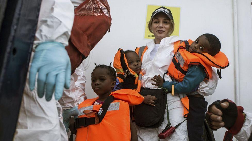 JUNCKERH.Una voluntaria de la ONG MOAS sostiene en sus brazos a dos pequeños rescatados del mar Mediterráneo