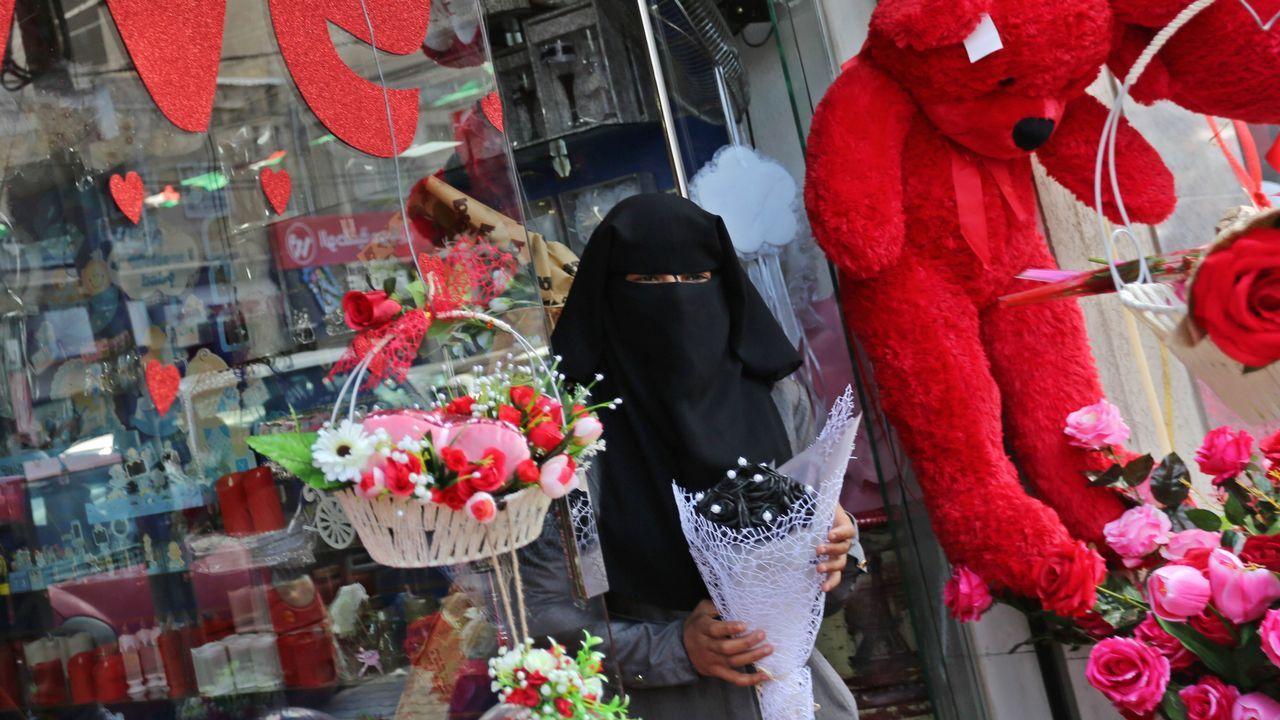 Una mujer palestina sale de una tienda de Gaza totalmente cubierta de regalos para San Valentín.