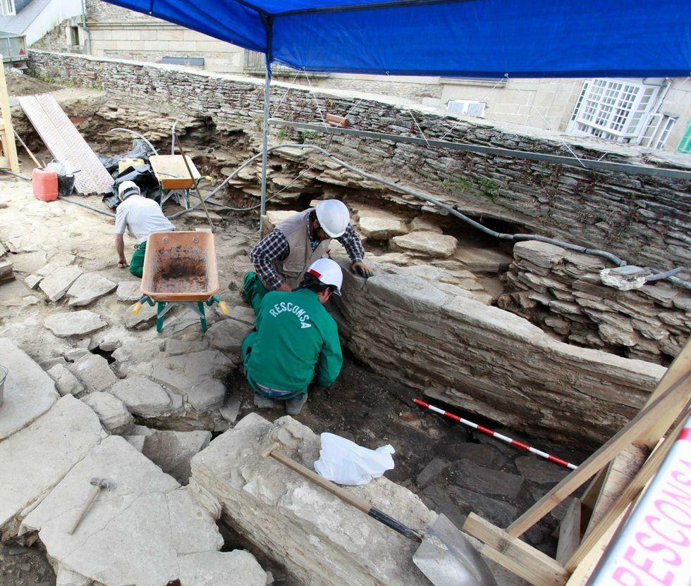 Los tres expertos de la Muralla con Aspnais.Los obreros trabajan en el muro que se supone formó parte de los cimientos de la torre del siglo XIV.