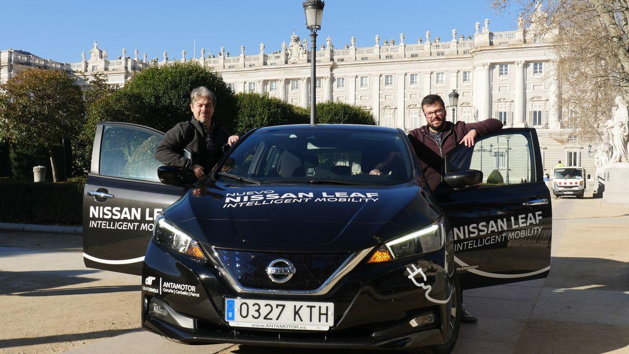 Óscar Ayerra junto a Iago García (de izquierda a derecha). Los periodistas de La Voz posan al día siguiente de completar el recorrido en 20 horas hasta Madrid en la Plaza de Oriente, con el Palacio Real a sus espaldas