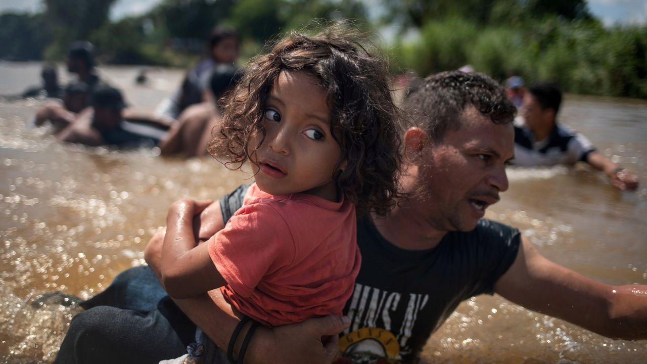 Un hombre lleva en brazos a una niña, ambos hondureños e integrantes de la caravana que avanza hacia EE. UU., cruzan el río Suchate en Ciudad Hidalgo (México)