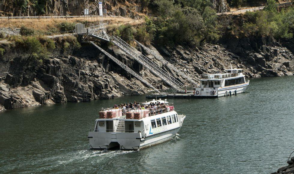 En primer plano, un barco de la Diputación de Lugo cargado de turistas frente al embarcadero de Doade. En la orilla ourensana se aprecian bien los efectos de la bajada de nivel del embalse, con las escaleras del pantalán con máxima inclinación.