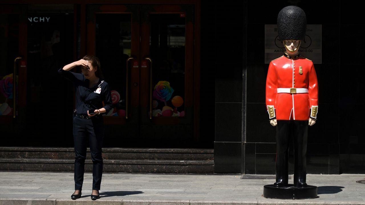 .Una mujer espera junto a la entrada de un peculiar supermercado de China.
