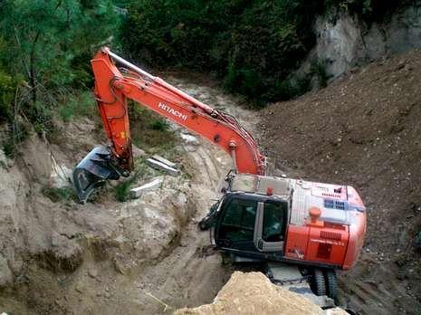 .Una máquina excavadora junto a los restos del castro.