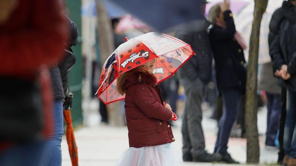 Una niña disfrazada y con paraguas entre el público que seguía el desfile en el barrio de la Estación