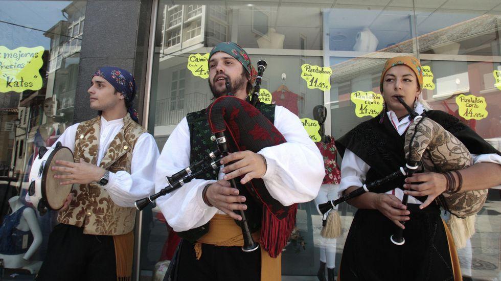 La procesión previa a la ofrenda floral, con la torre del castillo de San Vicente de fondo.Uno de los grupos participantes en el Día do Gaiteiro, en plena actuación frente a la plaza de abastos