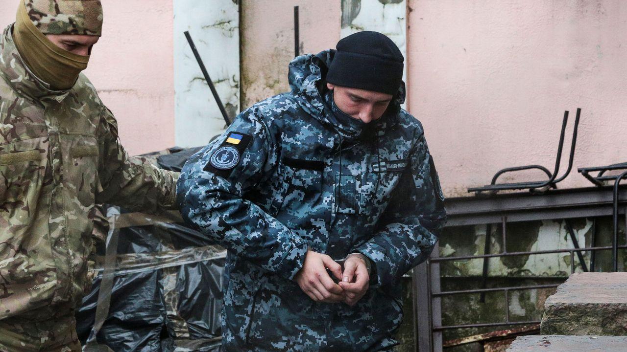 Un agente del servicio secreto traslada a uno de los marinos ucranianos al tribunal de Sumferopol