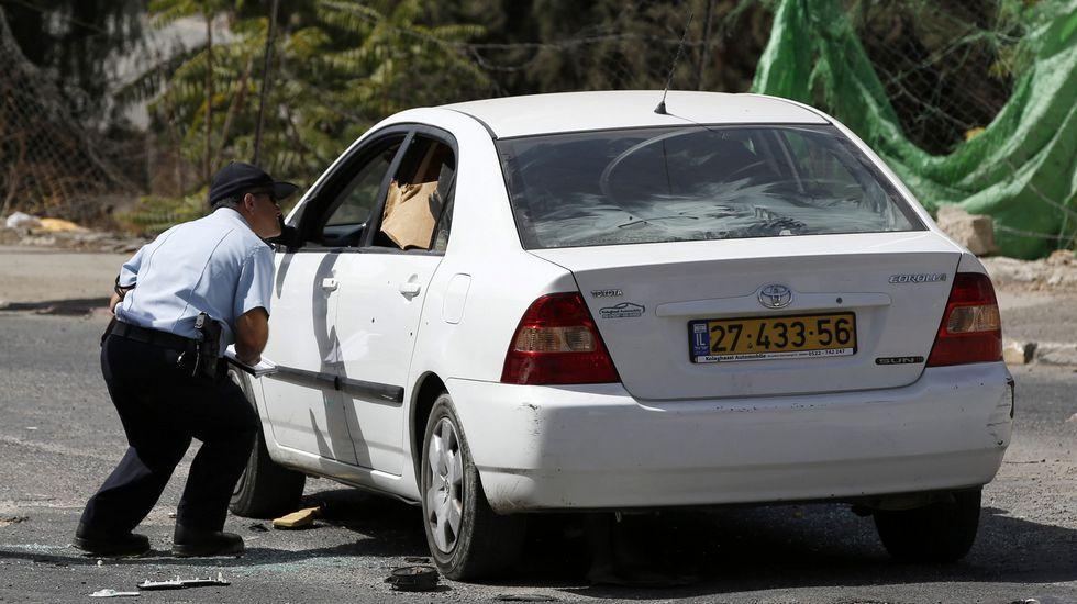 .Un policía israelí analiza el coche del tirador