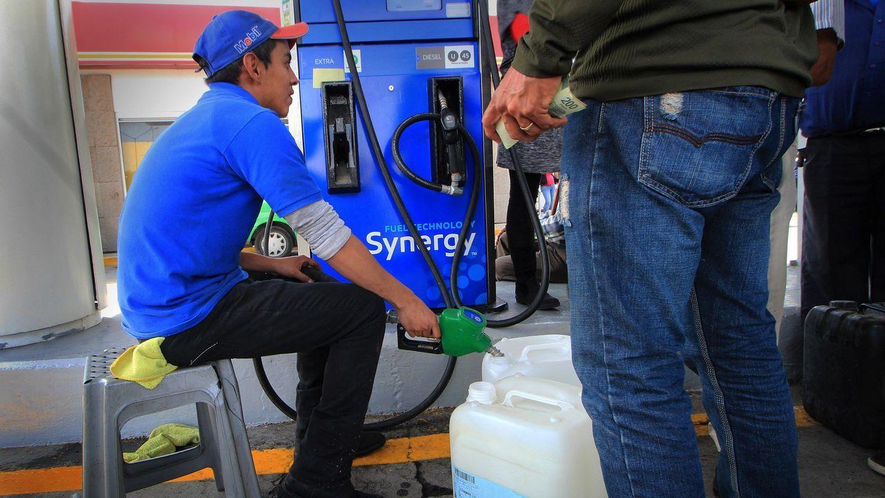 Un empleado de una gasolinera despacha combustible racionado en México