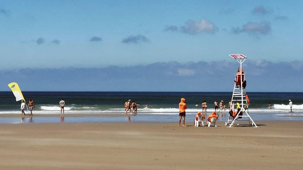 .Bañistas y el equipo de salvamento en la playa de Xagó