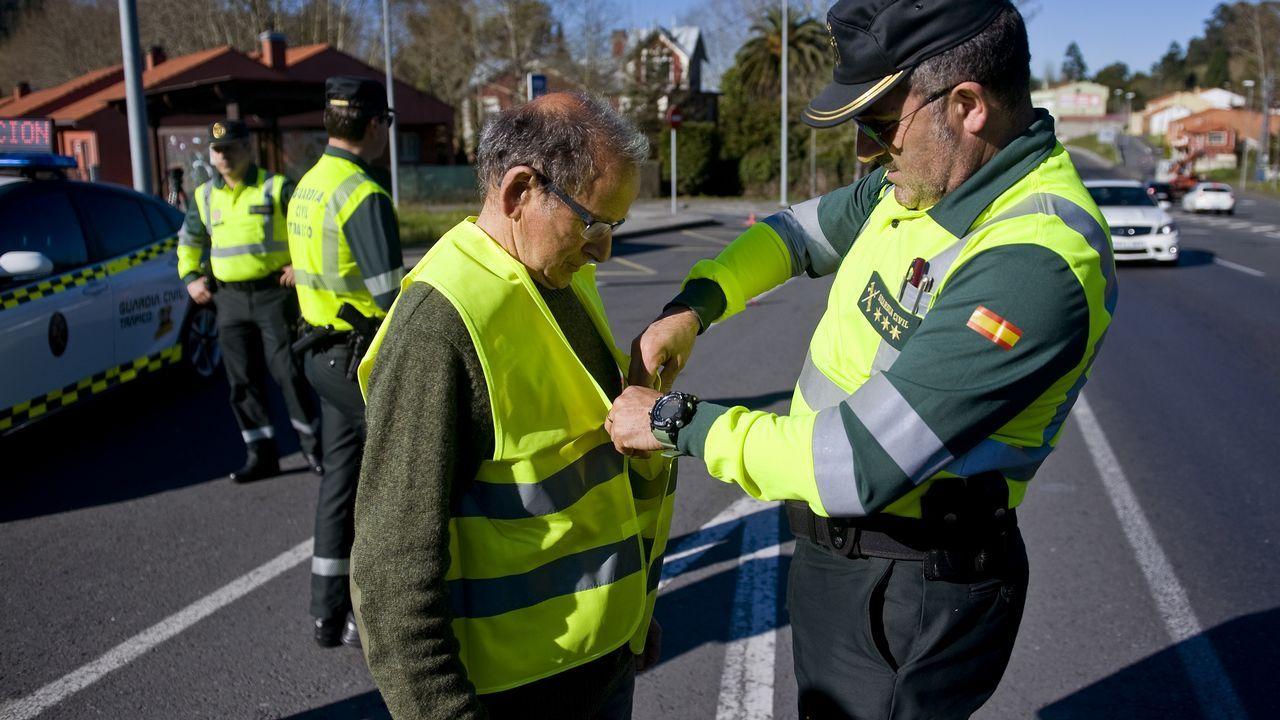 Un guardia civil le pone un chaleco reflectante a un peatón que caminaba cerca del lugar de la presentación de la campaña para evitar atropellos