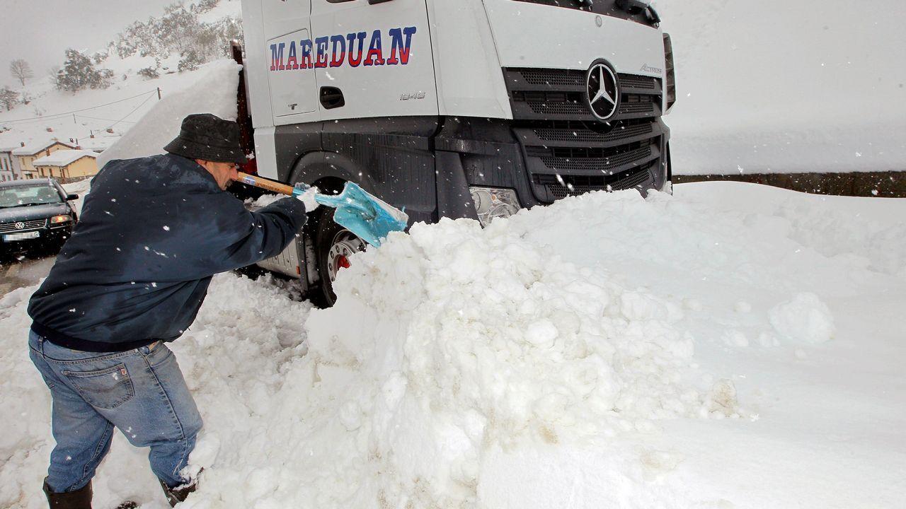 La nieve ya cubre Pajares.Un camionero trata de desploquear su camión de la nieve, en el pueblo de Pajares