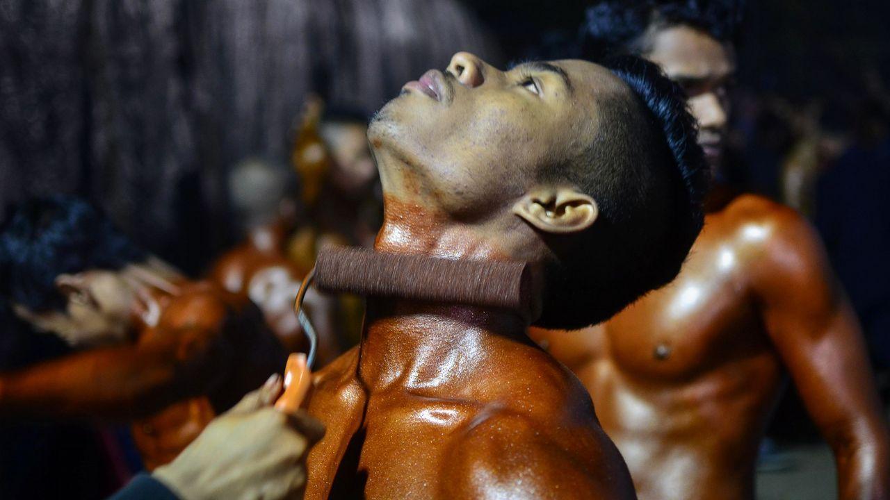 Un competidor de culturismo recibe un producto de bronceado antes de un concurso en Assam, en el noroeste de la India