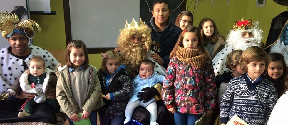 Varios niños de Coirós posan con sus majestades en el local social de Queirís.