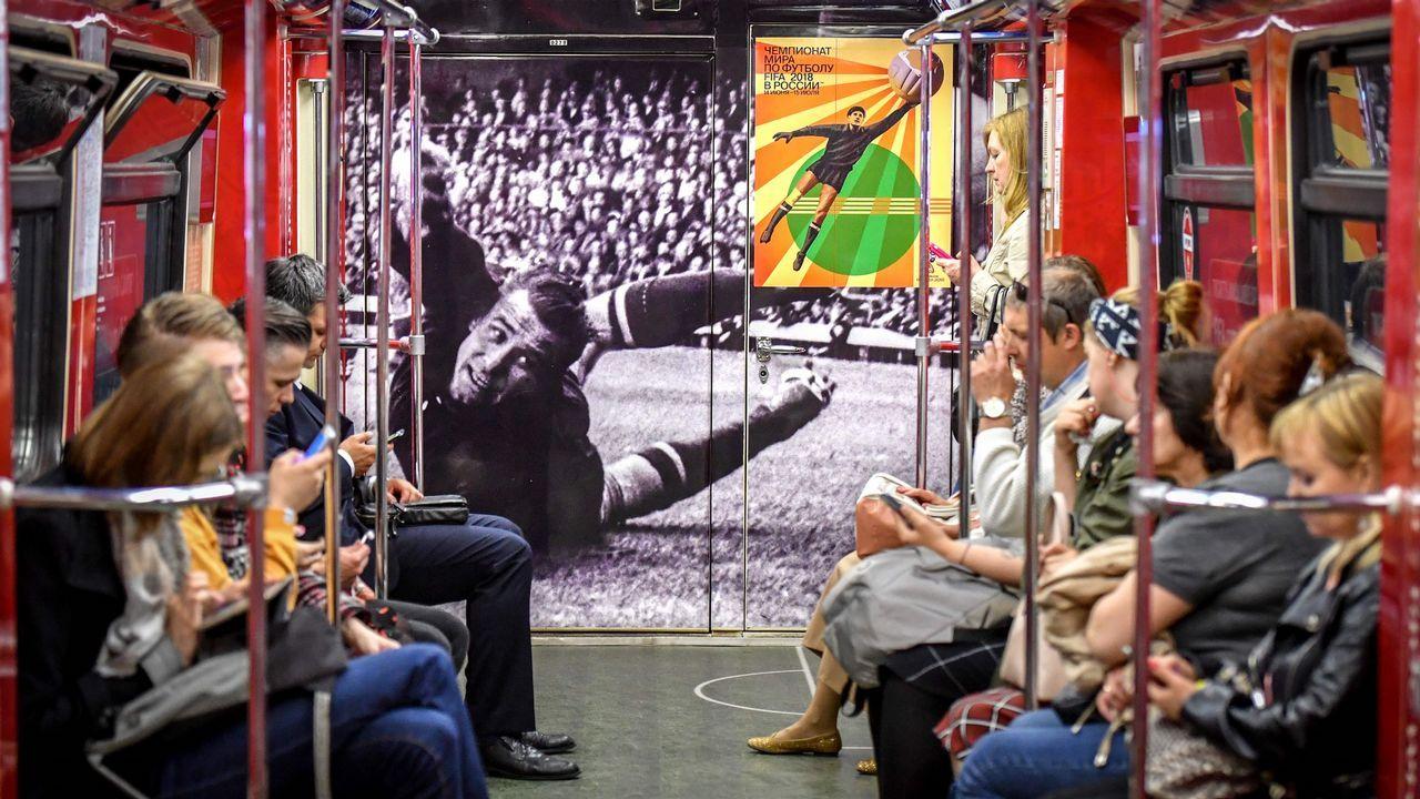 Un grupo de viajeros, en el metro de Moscú con una imagen del portero soviético Lev Yashin