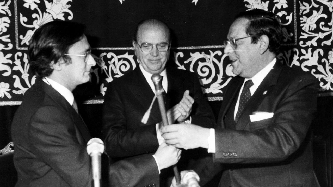 .Carlos Pajares recibe el bastón de mando como nuevo rector de la Universidad de Santiago de manos de Suárez Núñez, su antecesor, y el presidente de la Xunta de Galicia Fernández Albor.