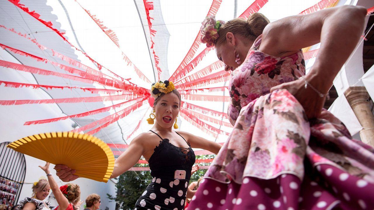 Mujeres vestidas con trajes de flamenca bailan en la calle Larios del centro histórico de la ciudad donde se celebra parte de la Feria de Málaga que este año ha recuperado un día más y se prolonga hasta el domingo 19 de agosto
