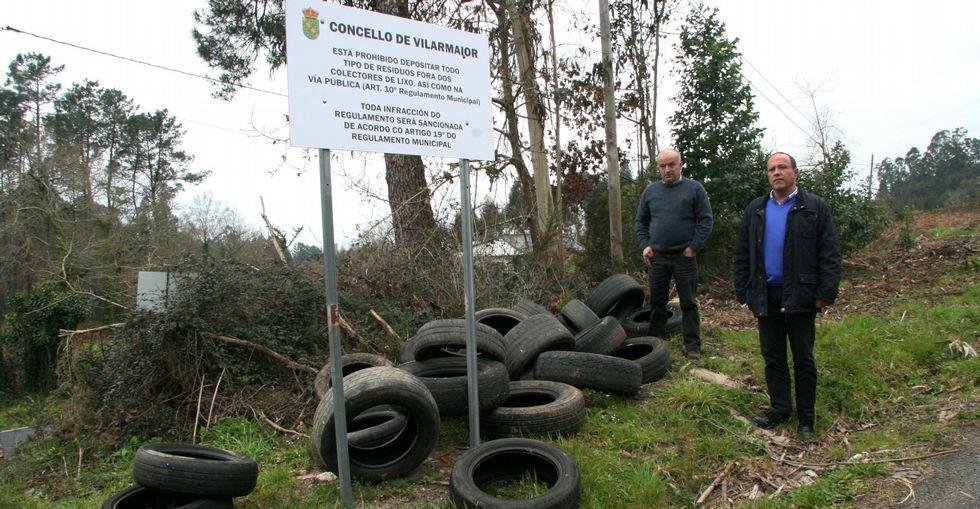 .El alcalde de Vilarmaior (derecha) muestra el vertido junto al cartel que prohíbe arrojar residuos.
