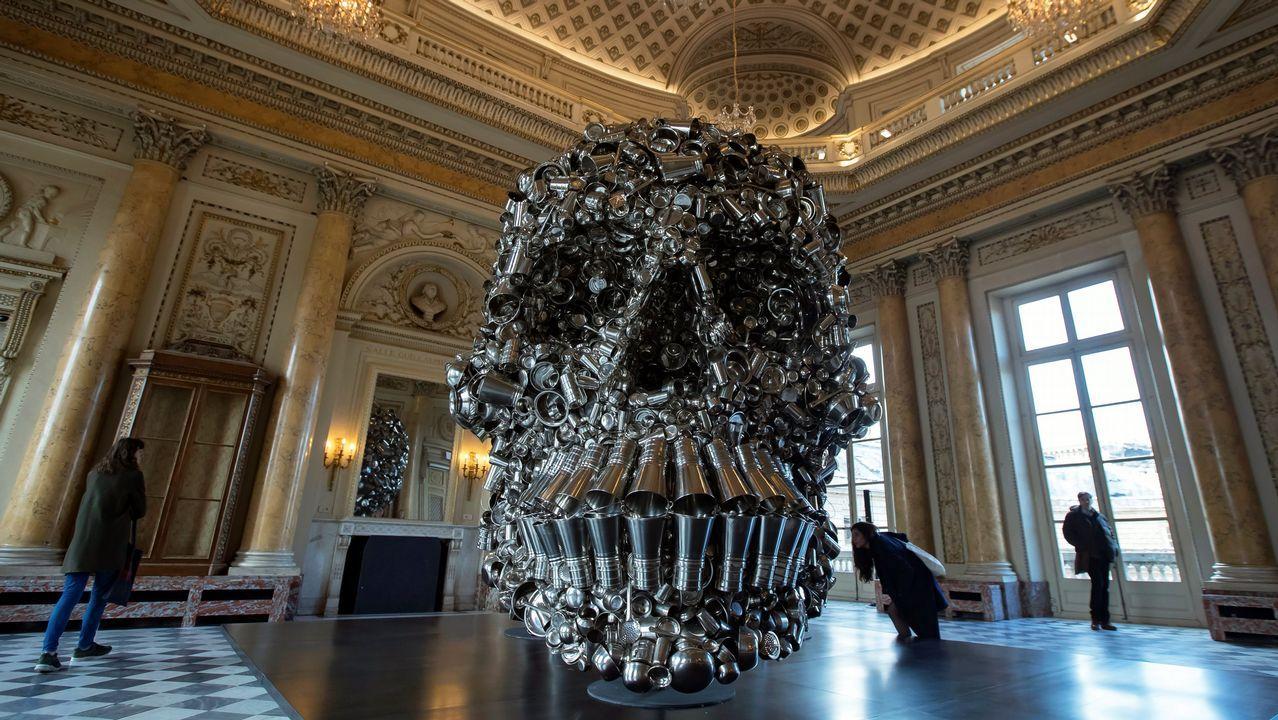 Varios visitantes observan la obra «Dios muy hambriento» del artista indio Subodh Gupta en una retrospectiva de su trabajo en el museo Monnaie de París (Francia)
