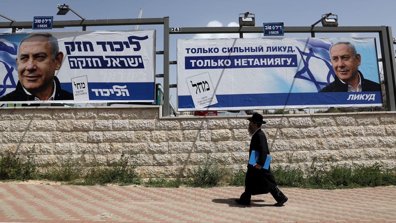 Un ultraortodoxo pasa por varios carteles electorales de Benjamin Netanyahu para las elecciones del martes