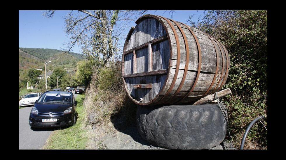 Un gran tonel con una rueda de tractor que le sirve de soporte da la bienvenida a los visitantes en Vilamor do Courel