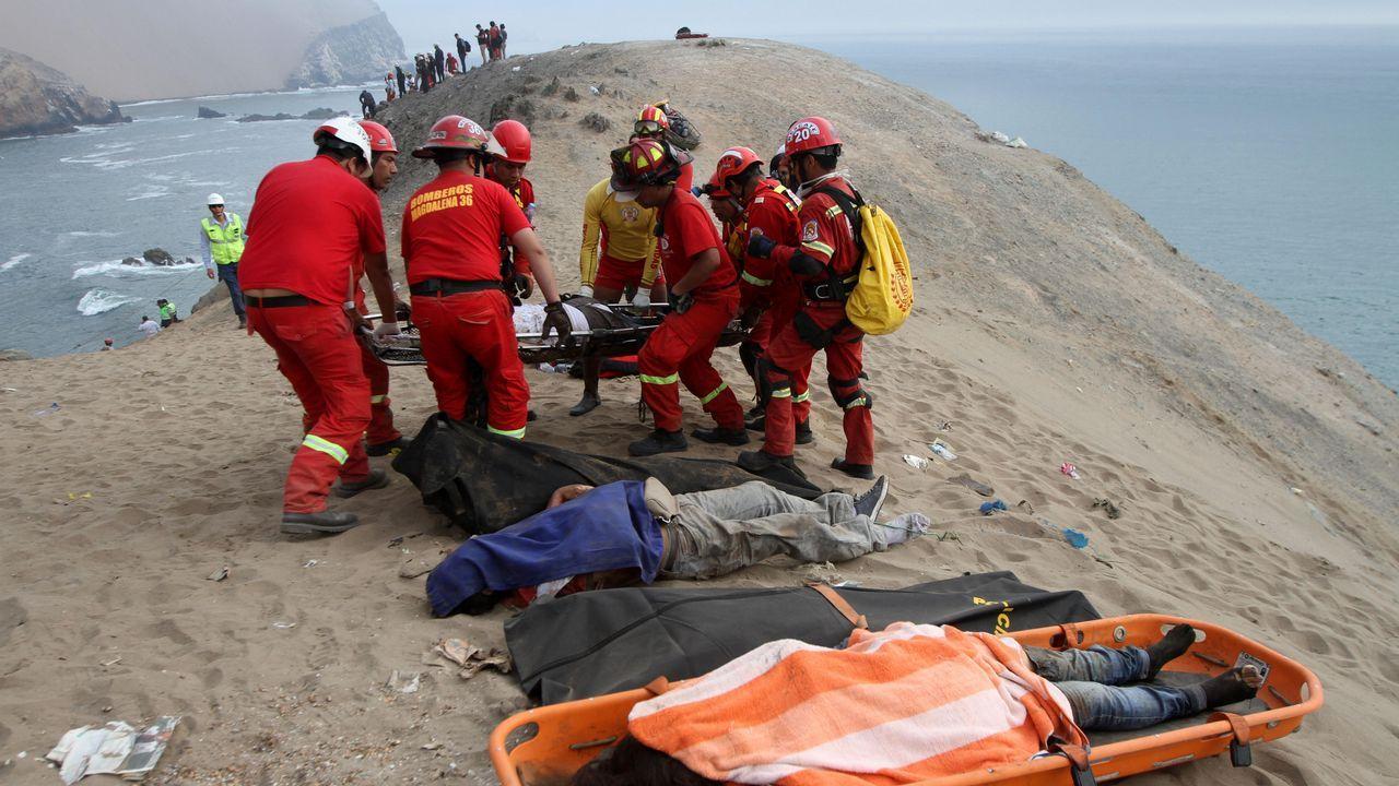 Un grupo de bomberos y policías durante las labores de rescate de las víctimas del autobús siniestrado en Perú