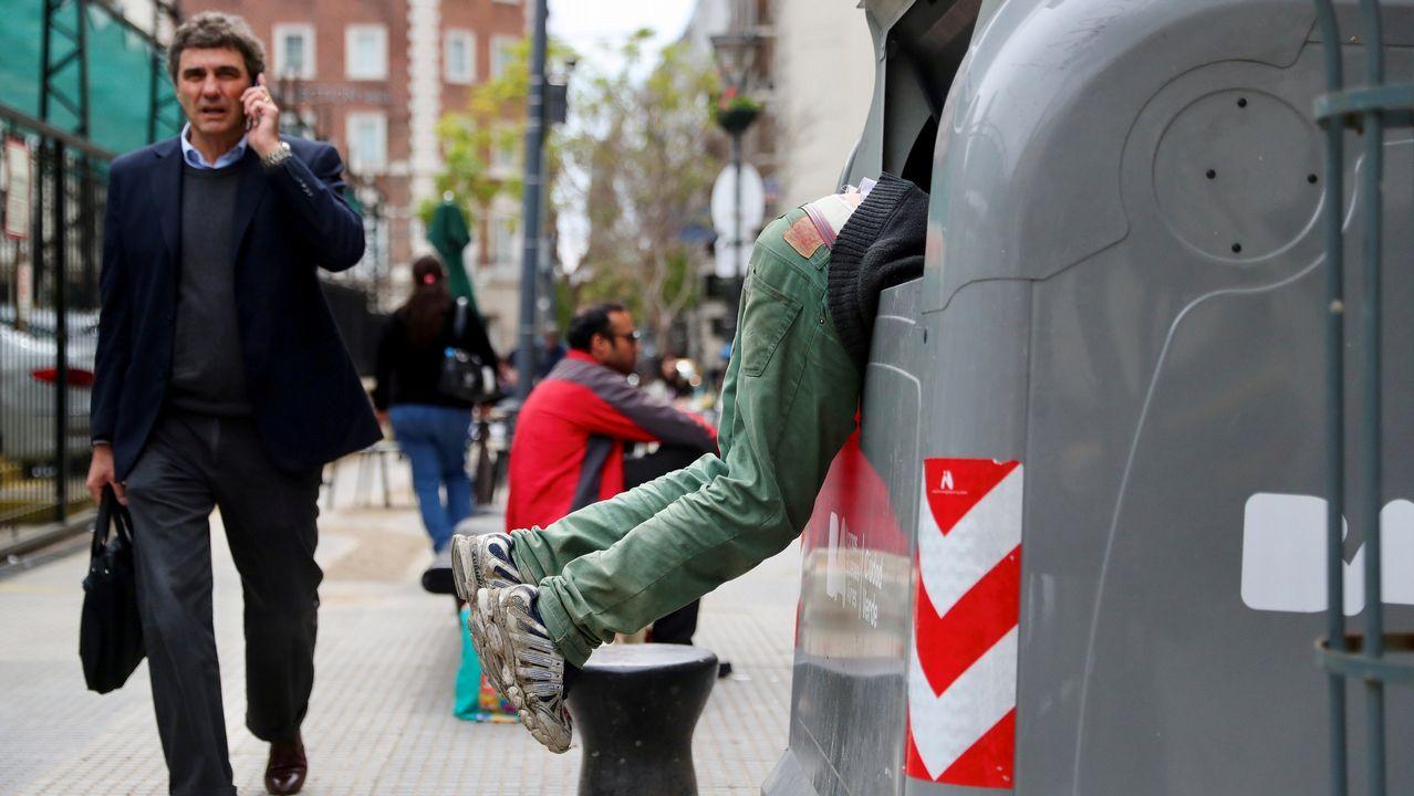 Un hombre busca dentro de la basura en el distrito financiero de Buenos Aires.