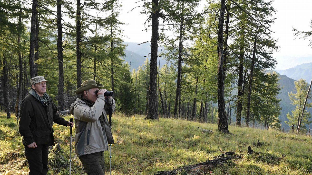 .Putin mira el paisaje a través de sus prismáticos acompañado del director del Servicio Federal de Seguridad, Alexander Bortnikov