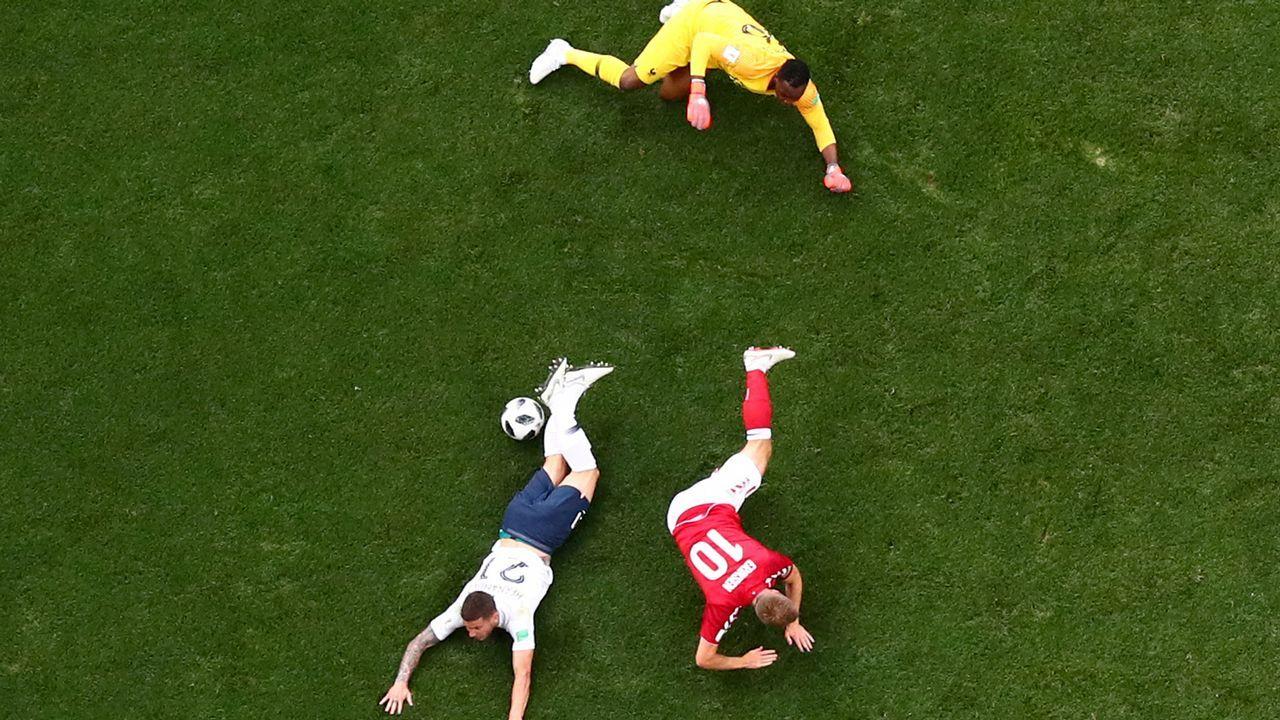 .Los jugadores franceses Mandala y Hernandez y el danés Eriksen, en el suelo durante un partido del Mundial