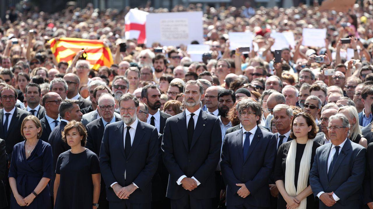 .El rey Felipe, la vicepresidenta del Gobierno, Soraya Sáenz de Santamaría, el presidente Mariano Rajoy, el presidente de la Generalitat, Carles Puigdemont y la alcaldesa de la ciudad, Ada Colau, guardan en la Plaza de Cataluña un minuto de silencio