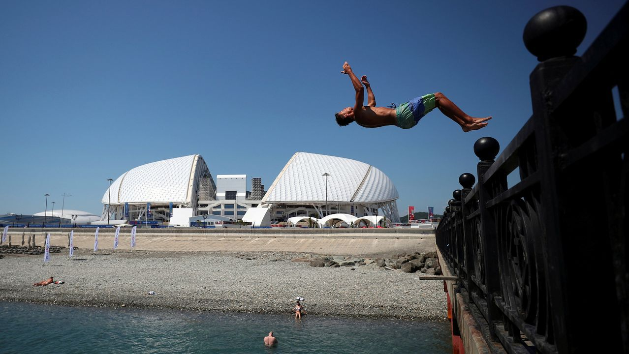 Un hombre se lanza al agua desde un puente con el estadio Fisht de fondo, en Sochi