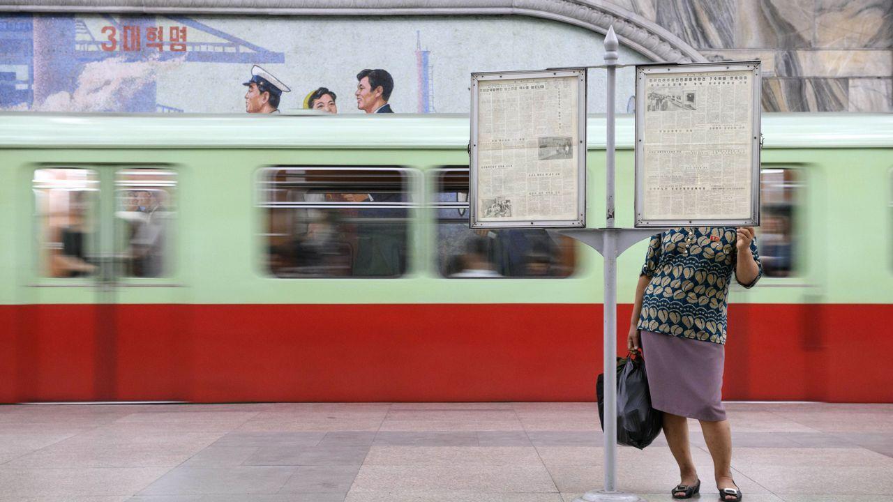 .Una pasajera lee un periódico en una estación de metro de Pyongyang, en Corea del Norte