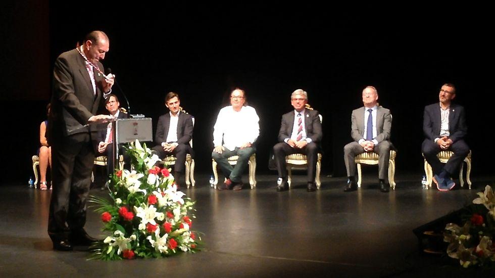 Quini sostiene, emocionado, la medalla que le reconoce como Hijo Adoptivo de Gijón ante los portavoces municipales, en el teatro Jovellanos