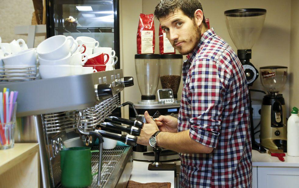 Luis Blanco maneja la máquina de café de su local en Vigo, The Coffe Land, que es su primer negocio propio.