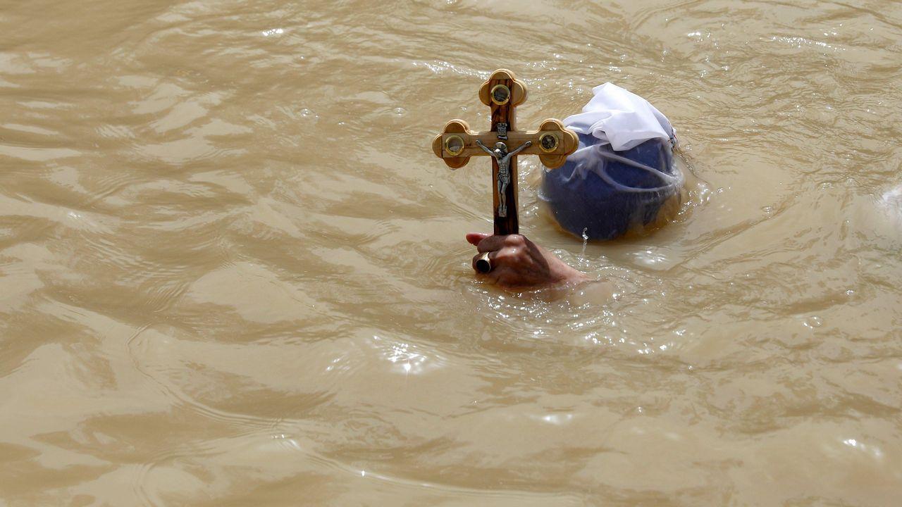 Un peregrino cristiano ortodoxo se sumerge en las aguas del río Jordán, en Palestina