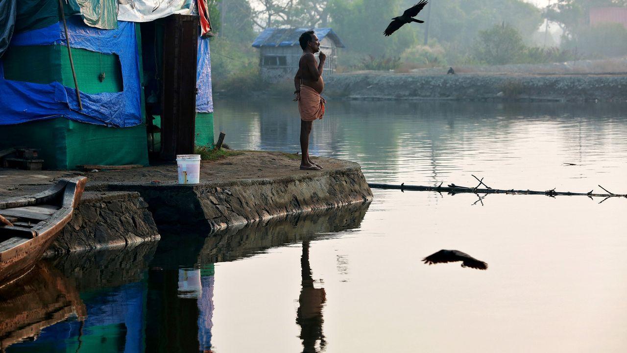 Un pescador se cepilla los dientes en la orilla del río Periyar, en las afueras de Kochi, India
