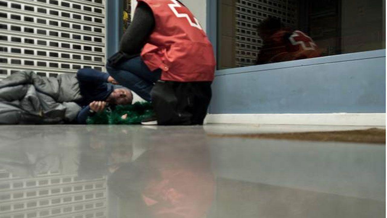 .Un voluntario atiende a una persona sin techo