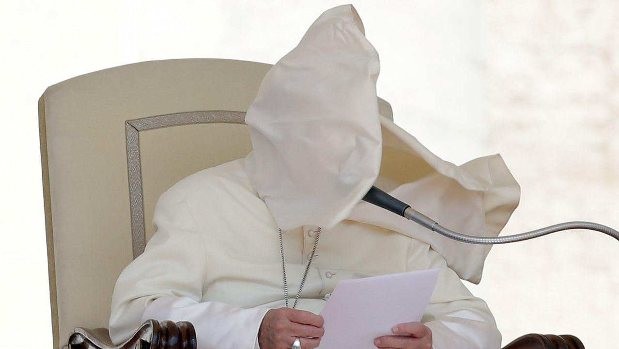 La muceta del papa Francisco le cubre la cara a causa de una ráfaga de viento durante la audiencia del miércoles en el Vaticano