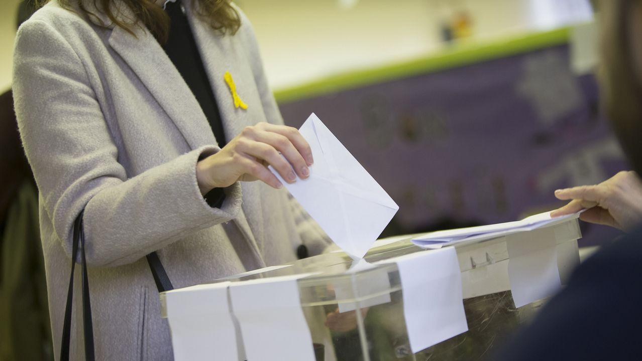 .Una mujer con un lazo amarillo deposita su voto en un colegio electoral de Barcelona