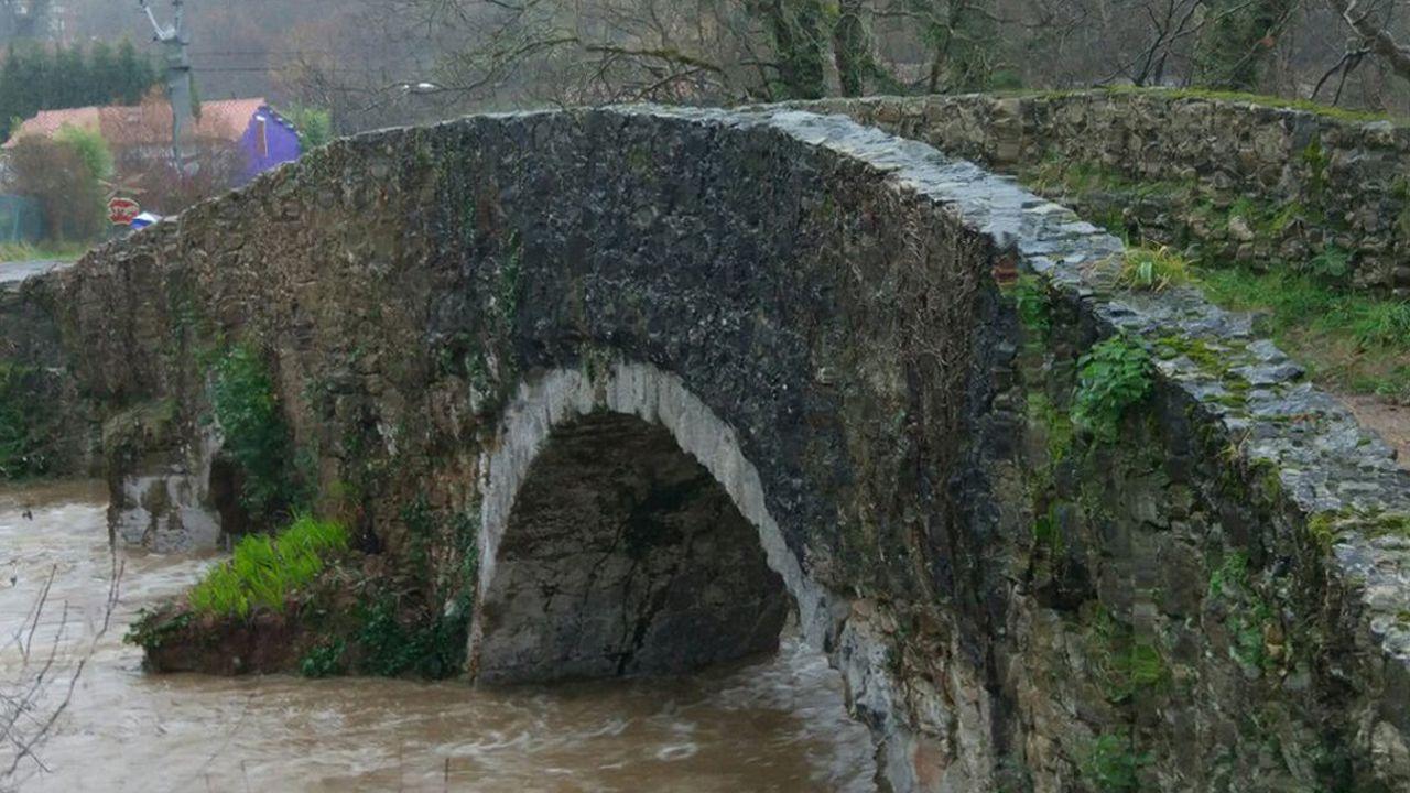 La nieve dificulta el tráfico en la autopista del Huerna.El abundante caudal del río Nora bajo el puente Romanón en La Pola