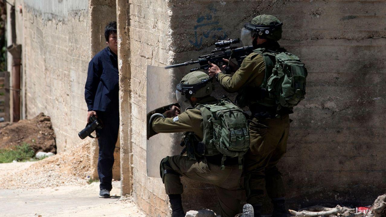.Un fotógrafo se cubre mientras las fuerzas israelíes permanecen tras un muro durante los enfrentamientos con manifestantes palestinos después de una manifestación semanal contra la expropiación de tierras palestinas por parte de Israel en la aldea de Kfar Qaddum, cerca de Nablus