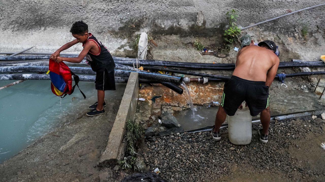 Un grupo de pasajeros consulta los vuelos en el Aeropuerto de Asturias.Venezolantos toman agua de una tubería abandonada ante la falta de electricidad y de suministro de agua potable