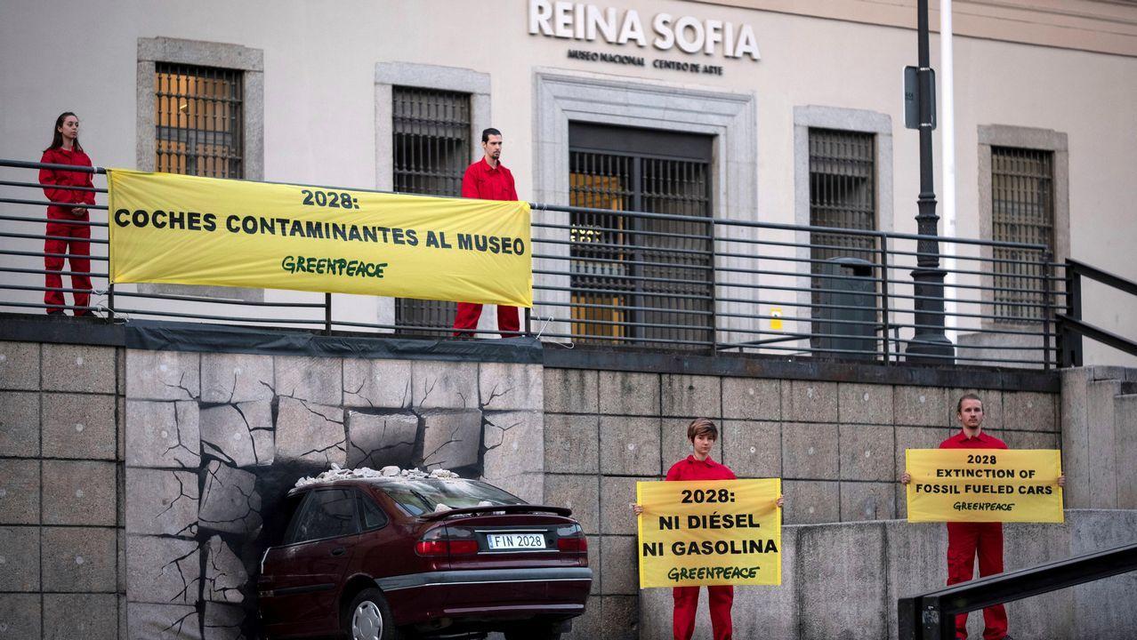 .Un coche «empotrado» en un museo para que las emisiones sean historia, una acción reivindicativa de Greenpeace, en la fachada del Reina Sofía de Madrid