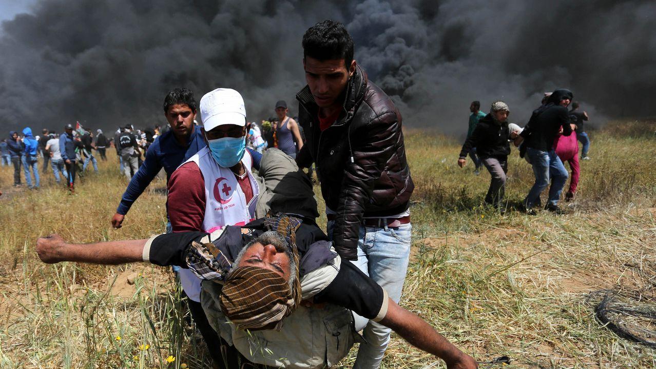 .Los manifestantes corren con los heridos entre la intenta humareda dejada por los neumáticos quemados