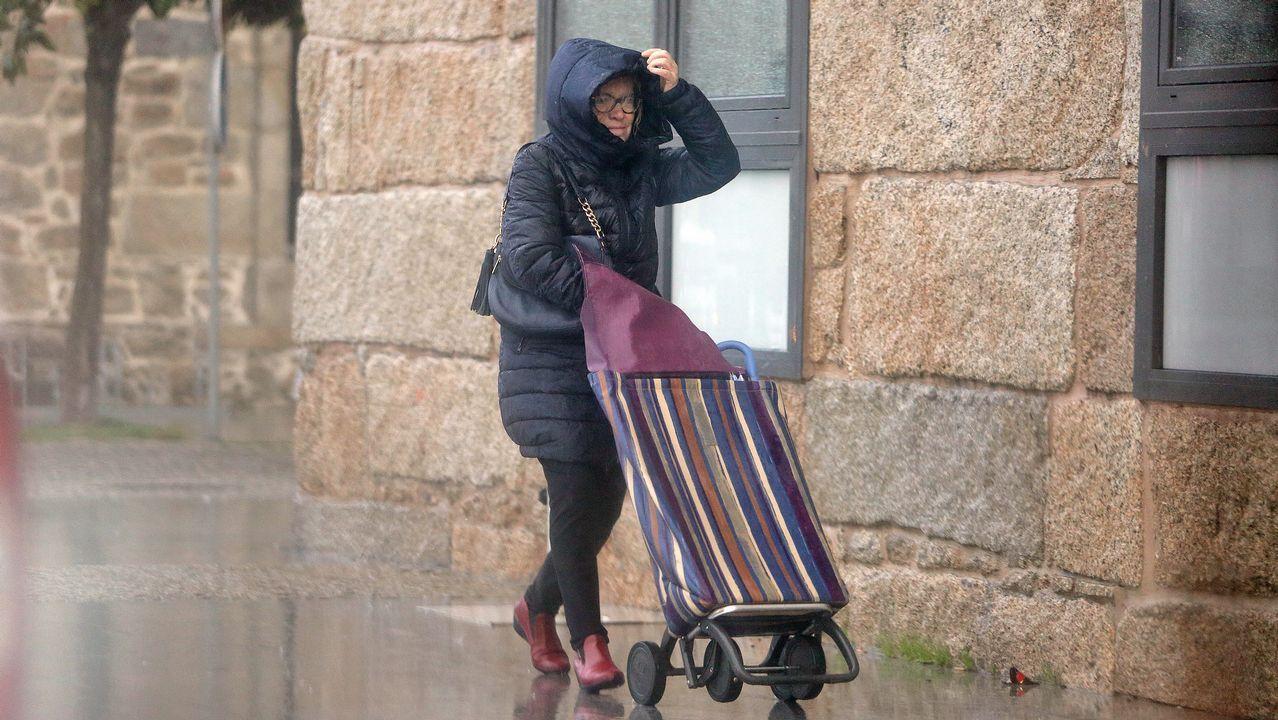 Altas temperaturas en Galicia.Una mujer se protege del mal tiempo en Arousa