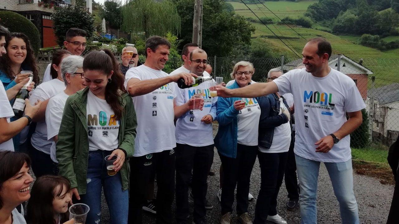 José Lago, a la derecha, brinda con sus vecinos por el premio al Pueblo Ejemplar para Moal