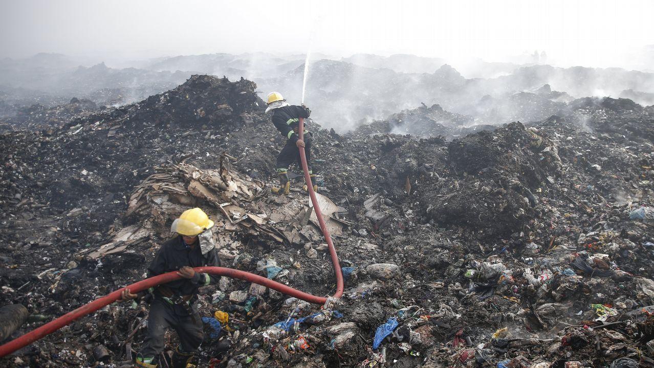 .Un grupo de bomberos trata de extinguir un fuego en el vertedero de Htain Bin, en Rangún (Birmania)