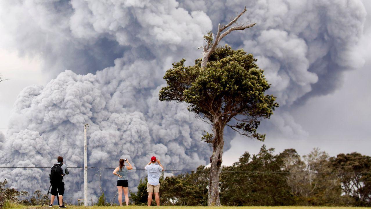 Varias personas observan la densa humareda procedente del volcán Kilauea, en Hawai