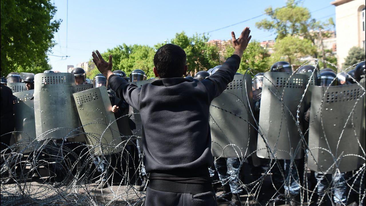 Un hombre se enfrenta a la policía durante una protesta en Armenia